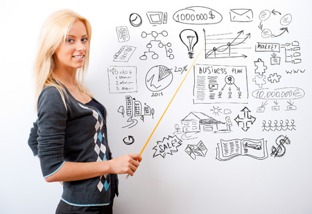 markerboard: Portrait of young teacher pointing on white marker board in modern educational center Stock Photo
