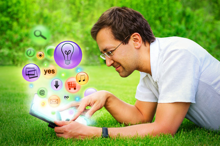 appearing: Adult man using his tablet computer at countryside. Different icons appearing from touchscreen