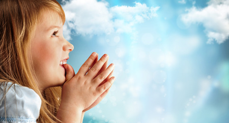Portrait of young smiling praying girl in blue dress against sky background. Lots of copyspace Stock Photo