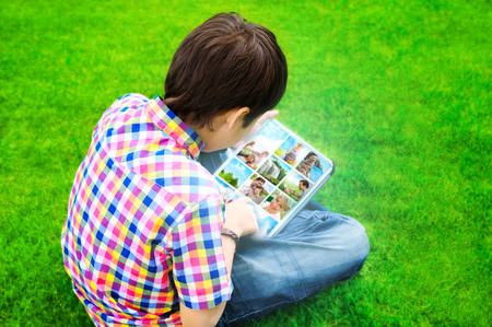 websurfing: Little boy sitting on grass and using tablet computer to watch or share photo and video files