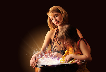 Young mother and her little daughter reading fairy book photo