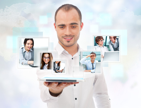 team vision: Adult businessman using his tablet computer to communicate his team. Virtual meeting technology for global business concept. Stock Photo