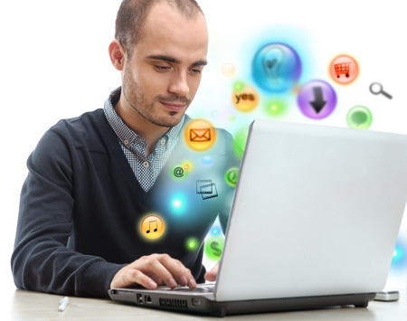 social worker: Young business man using his laptop for multimedia and site surfing  Different icons appearing from the screen isolated Stock Photo