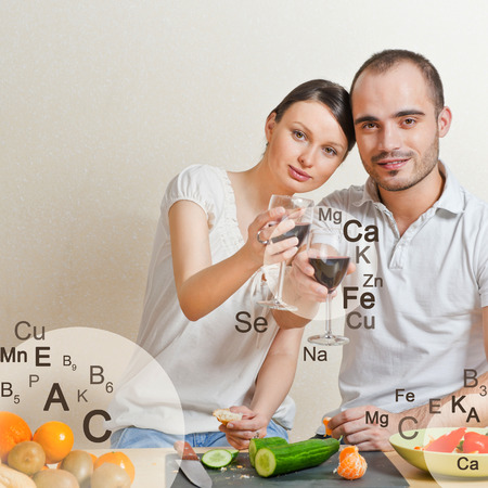 microelements: Young lovely couple cooking a balanced diet. Big copyspace. Vitamins and microelements symbols are around them.