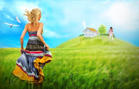 Mujer joven que se ejecuta a través del campo a casa y familia de su sueño. Los sueños se hacen realidad con el concepto de hipoteca Foto de archivo