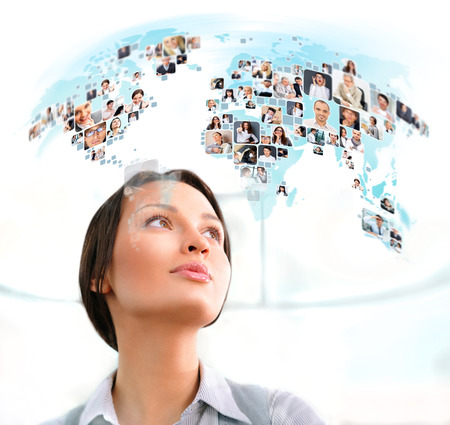 information international: Young successful woman looking at world map with profile photos of her colleagues Stock Photo