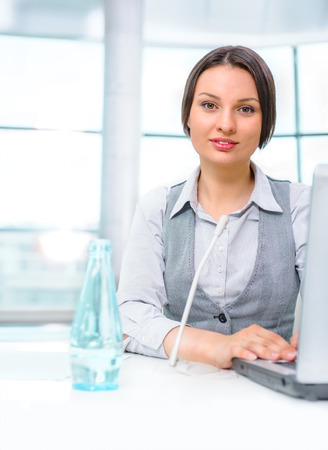 Smiling pretty business woman with microphone. She is salesperson or support team worker Stock Photo