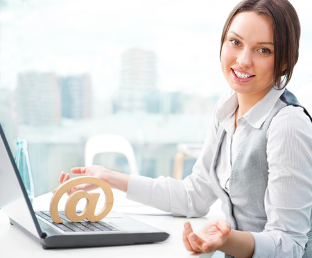 Portrait of a cheerful Business woman sitting on her desk and smiling. At symbol on her laptop photo