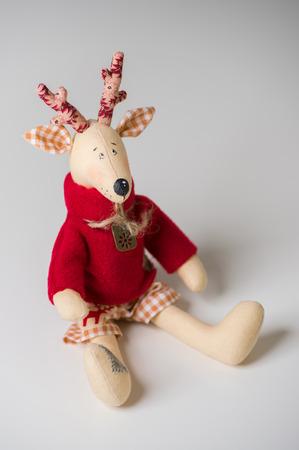 Handmade toy vintage Christmas deer sitting on light background photo