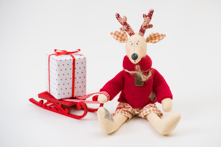 Handmade toy vintage Christmas deer sitting on light background with gift box photo