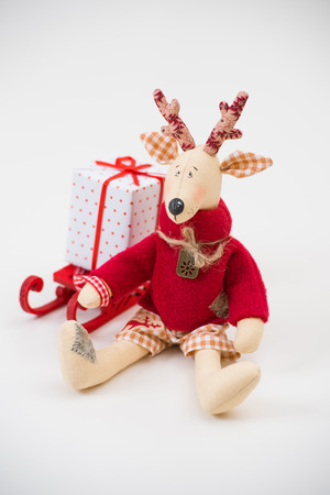 Handmade toy vintage Christmas deer sitting on light with gift box photo