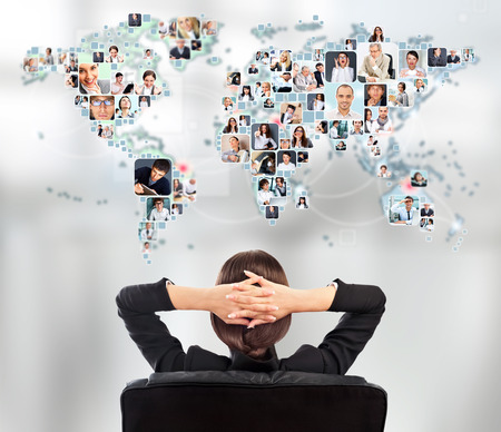 business networking: Portrait of young woman communicating with her friends across the world. Sitting against world map with photo of people. International communications concept