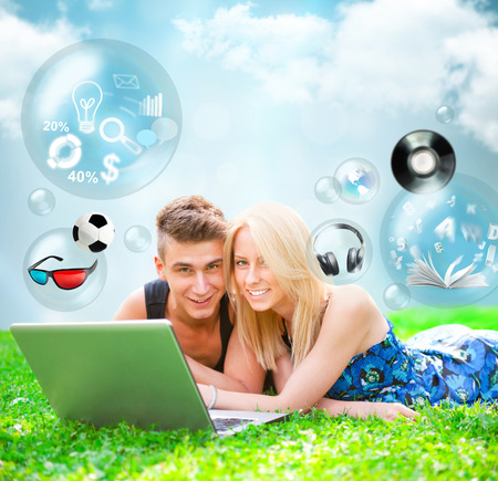 Portrait of young people outdoor resting on green grass and using laptop. Different objects are flying from the screen