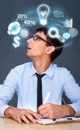 Adult business man working and different icons of functionality are flying around his head photo