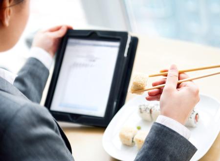 Mujer bonita celebraci�n de sushi con los palillos y la lectura de noticias con su Tablet PC y wifi gratuito en la cafeter�a se ofrecen almuerzos de negocios