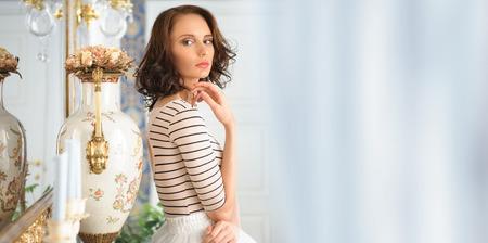 Beautiful woman standing near mirror. Beauty fashion portrait photo