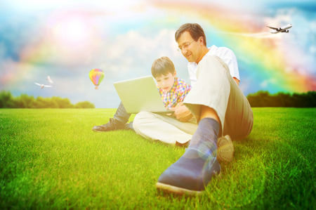 Adult man and his little son sitting on a grass at park and having fun or educating on laptop. Idyllic background - bright future concept photo