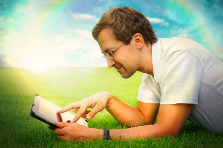 Adult man at summer park resting on weekend using his tablet computer to communicate friends or have fun with new photo, video and audio photo