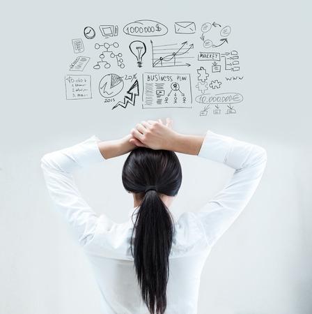 mujer reflexionando: Vista posterior de la joven mujer de negocios pensando en sus planes con las manos detrás de la cabeza