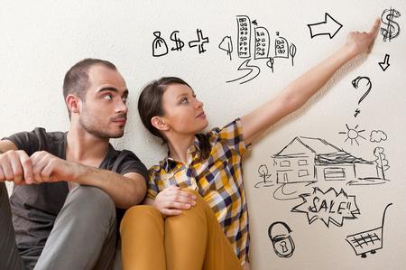 Close-up portret van volwassen paar zitten op de vloer in hun appartement en de planning van de renovatie van hun nieuwe appartement, terwijl rust tijdens huishoudelijk werk