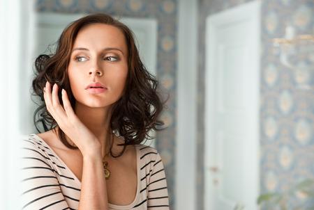 Beautiful woman standing near window. Beauty fashion portrait photo