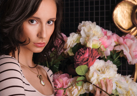 Portrait of young gorgeous woman with flowers at dark room with tile on walls photo