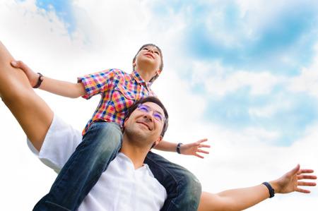 familie: Portret van glimlachende vader die zijn zoon piggyback rit buitenshuis tegen hemel