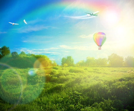 air animals: Beautiful image of stunning sunset with atmospheric clouds and sky over vibrant fields in  countryside landscape with hot air balloon, birds and airplane flying high