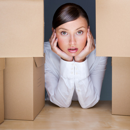 Portrait of young woman surrounded by lots of boxes. Lots of work concept. Stock Photo