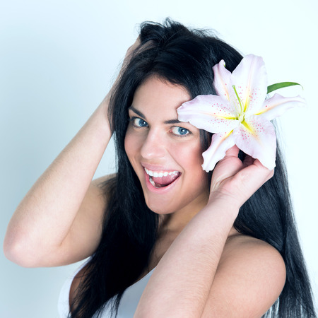 unblemished: Pretty beautiful woman with healthy skin and pink lily in her hairs laughing and looking at camera