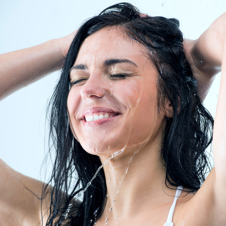 Woman washing her head while showering with happy smile and water splashing.  photo