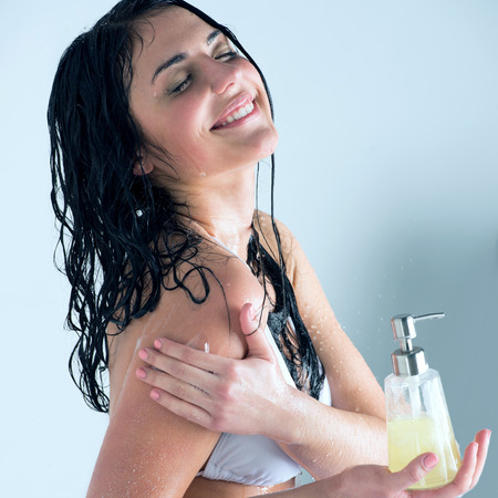 Beautiful girl showering. Holding glass bottle with shower gel and washing herself while water is splashing photo