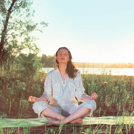 Beautiful young woman doing yoga sitting near the lake early in the morning. Vintage filter photo photo