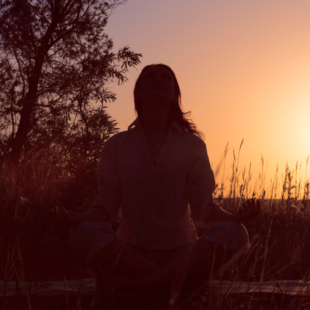 Silhouette of a beautiful Yoga woman on sunrise and rays of light surrounding her. Retro filter photo photo
