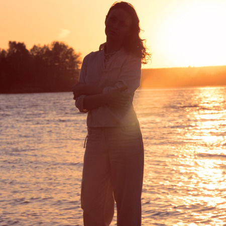 Young woman walking on beach under sunset light.  photo