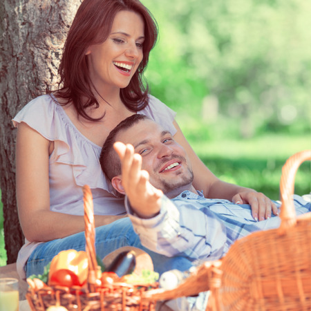 Adult couple picnicking in the park under the tree. Retro style photo photo