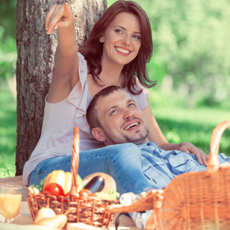 picnicking: Adult couple picnicking in the park under the tree. Retro style photo