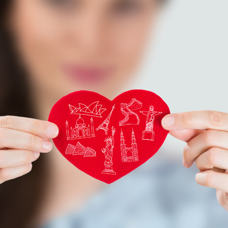 touristic: Female holding heart with her arms and famous touristic symbols are on this heart. Traveling addiction concept