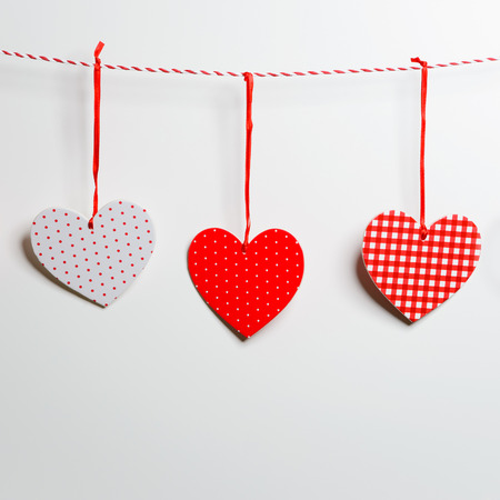Red textured hearts hanging on white background photo