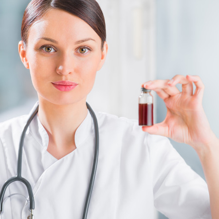 blood test: Portrait of pretty female laboratory assistant analyzing a blood sample at hospital
