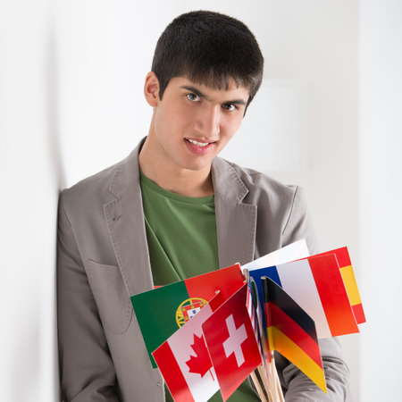 Mixed ethnicity handsome man leaning on white wall and holding many countries flags photo
