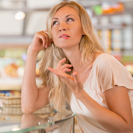 hesitating: Beautiful young woman standing near supermarket showcase full of different products and deciding what to buy Stock Photo