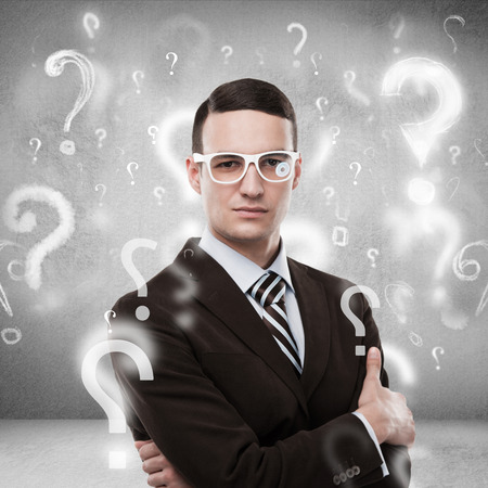 Handsome business man with question marks above his head photo