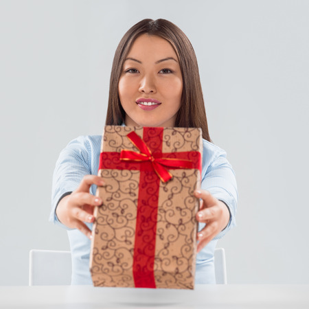 Portrait of young business woman sitting at her desk with a gift box photo