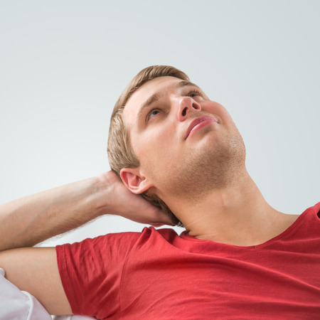 Portrait of a handsome young man looking upwards while relaxing and dreaming at home Stock Photo