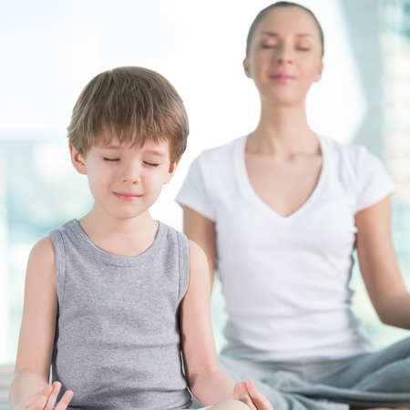 calming: Mother and son doing yoga exercise at home - focus on son