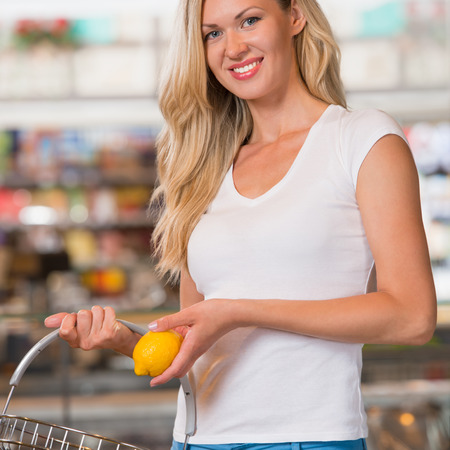 Casual woman grocery shopping at organic food section and looking happy at camera photo