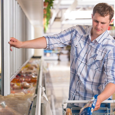 Man in a supermarket standing in front of the freezer looking for his favorite frozen food photo
