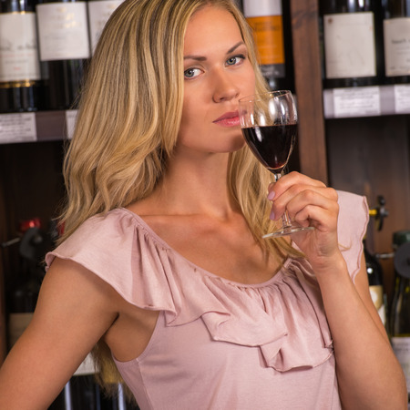 Woman in a supermarket degustating red wine photo