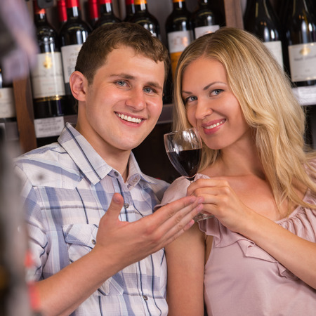 degustating: Young couple degustating red wine at supermarket